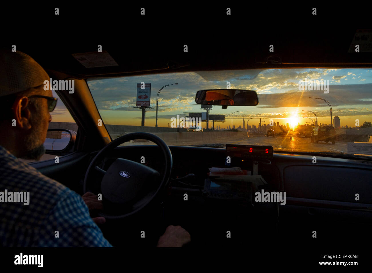 Taxi driver and the Manhattan skyline at sunset, Manhattan, New York City, New York, United States - Stock Image