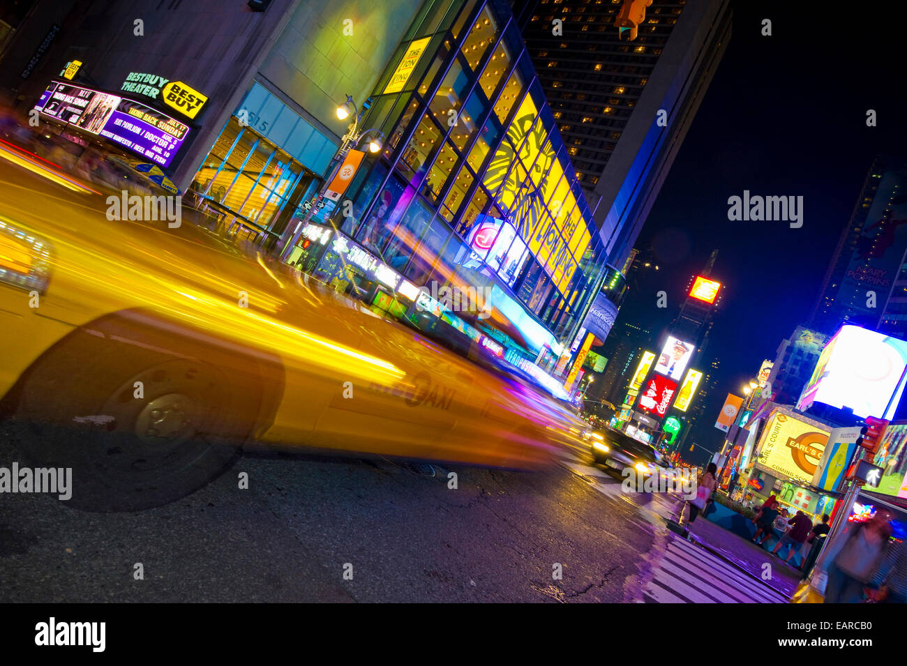 Neon signs and a taxi with motion blur in Times Square, Manhattan, New York City, New York, United States - Stock Image