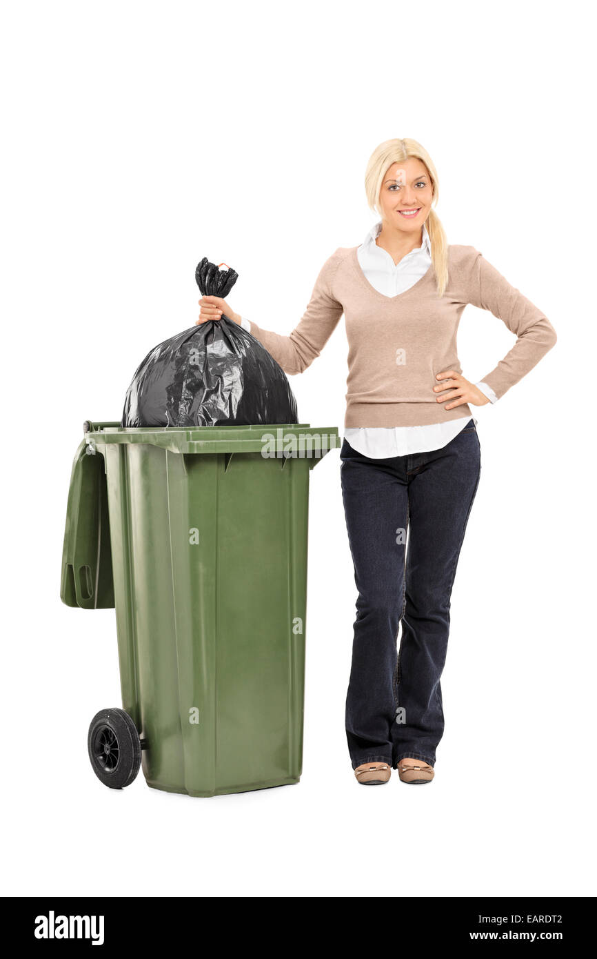 Full length portrait of a young woman throwing out the trash isolated on white background - Stock Image