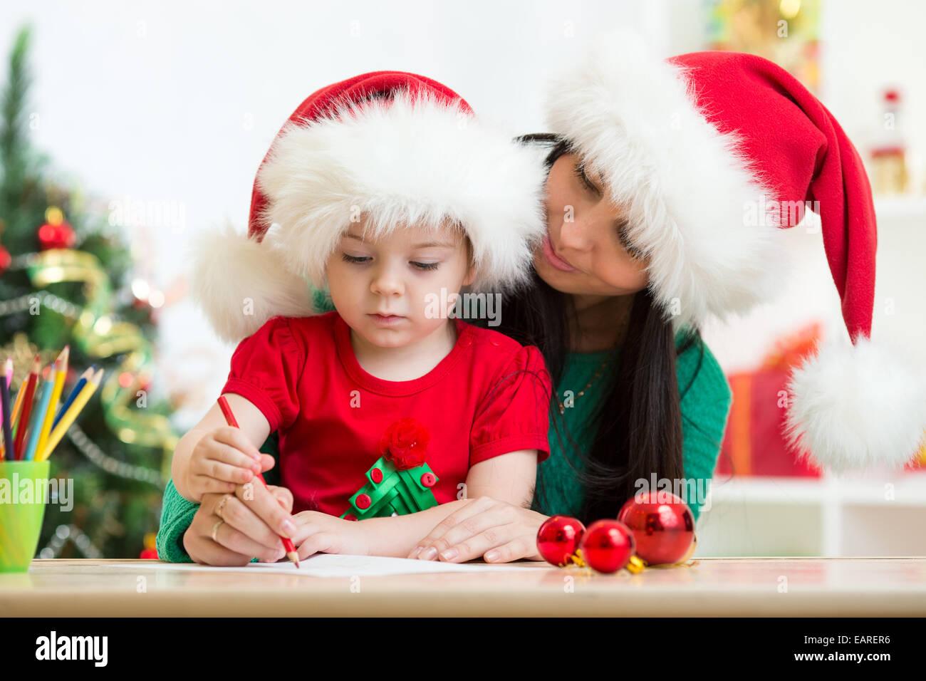 Child girl and mom writing christmas letter to Santa - Stock Image