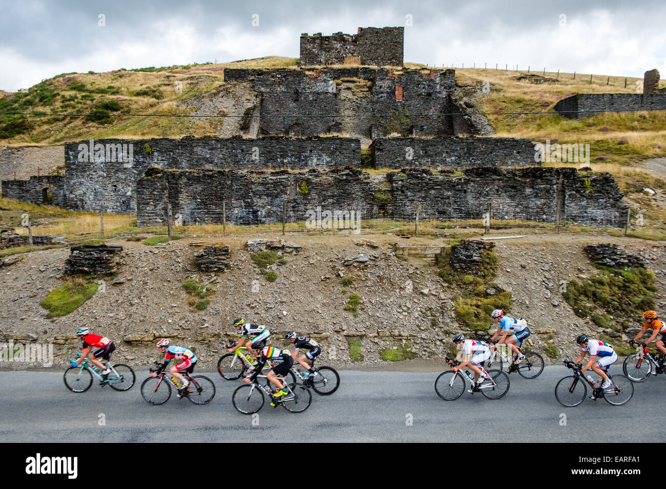 Professional cyclists passing the ruined lead mines in the 'Tour of the Mining Valleys' cycle race Ceredigion - Stock Image