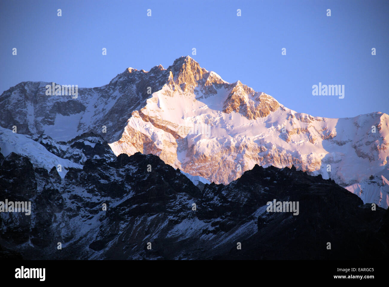 The sun rises on a Himalayan peak close to Kangchenjunga in the Indian state of Sikkim - Stock Image