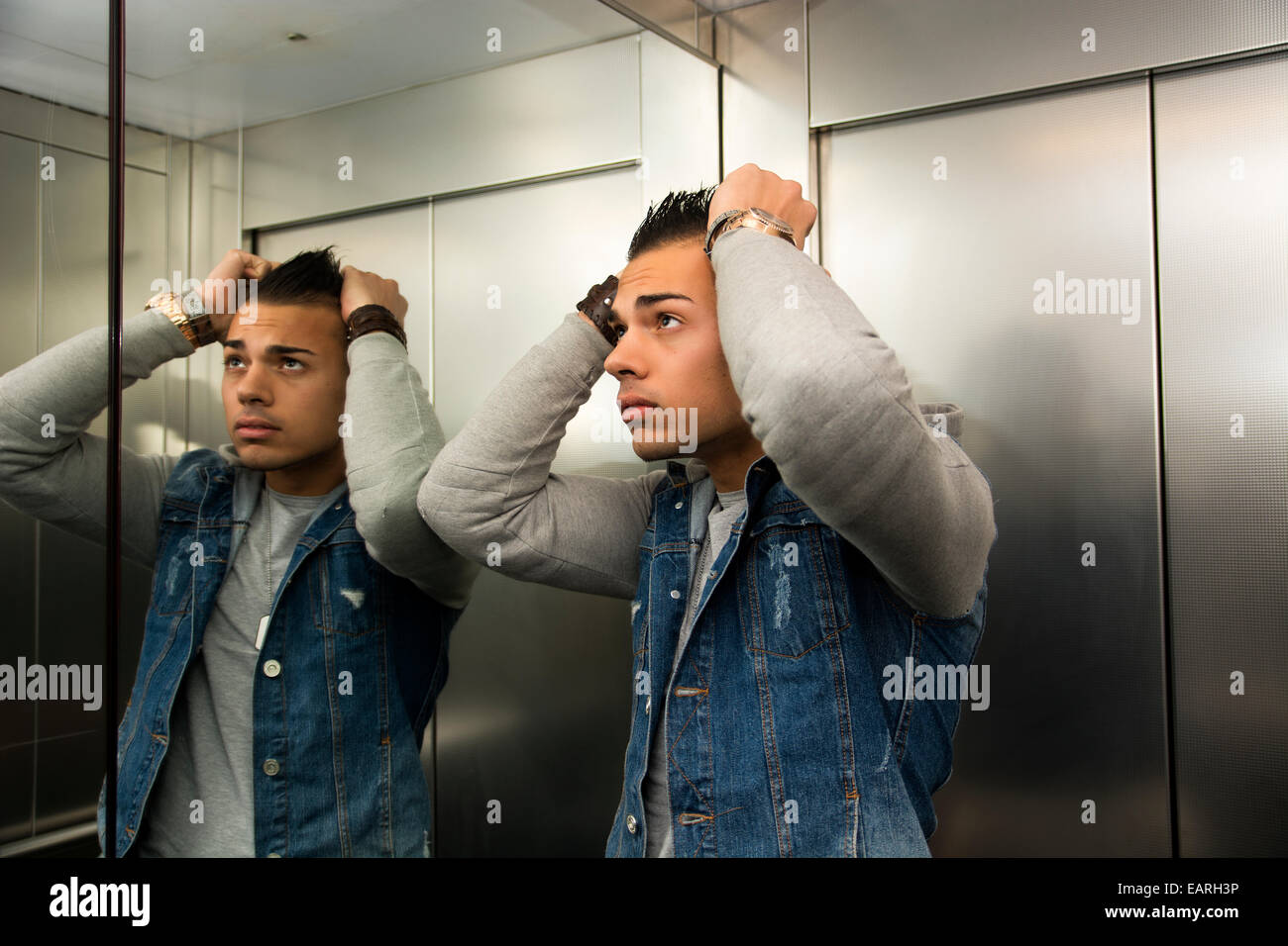 Scared young man desperate in stuck elevator with hands on his head - Stock Image