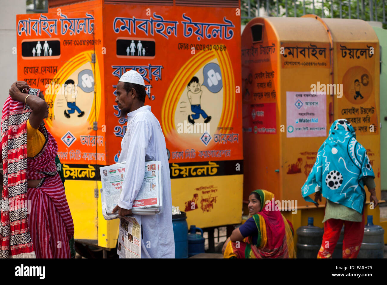 A paper saller making conversation with toilet cleaner infront of Itinerant Mobile toilet beside street in Dhaka. - Stock Image