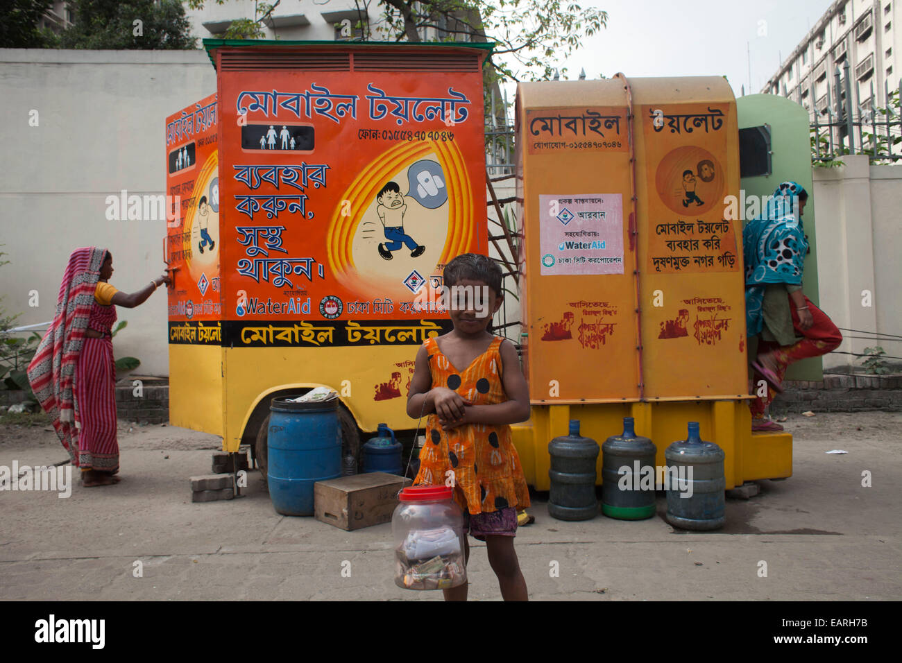 A street child hawcker in front of Itinerant Mobile toilet beside street in Dhaka. Inadequate sanitation in South - Stock Image