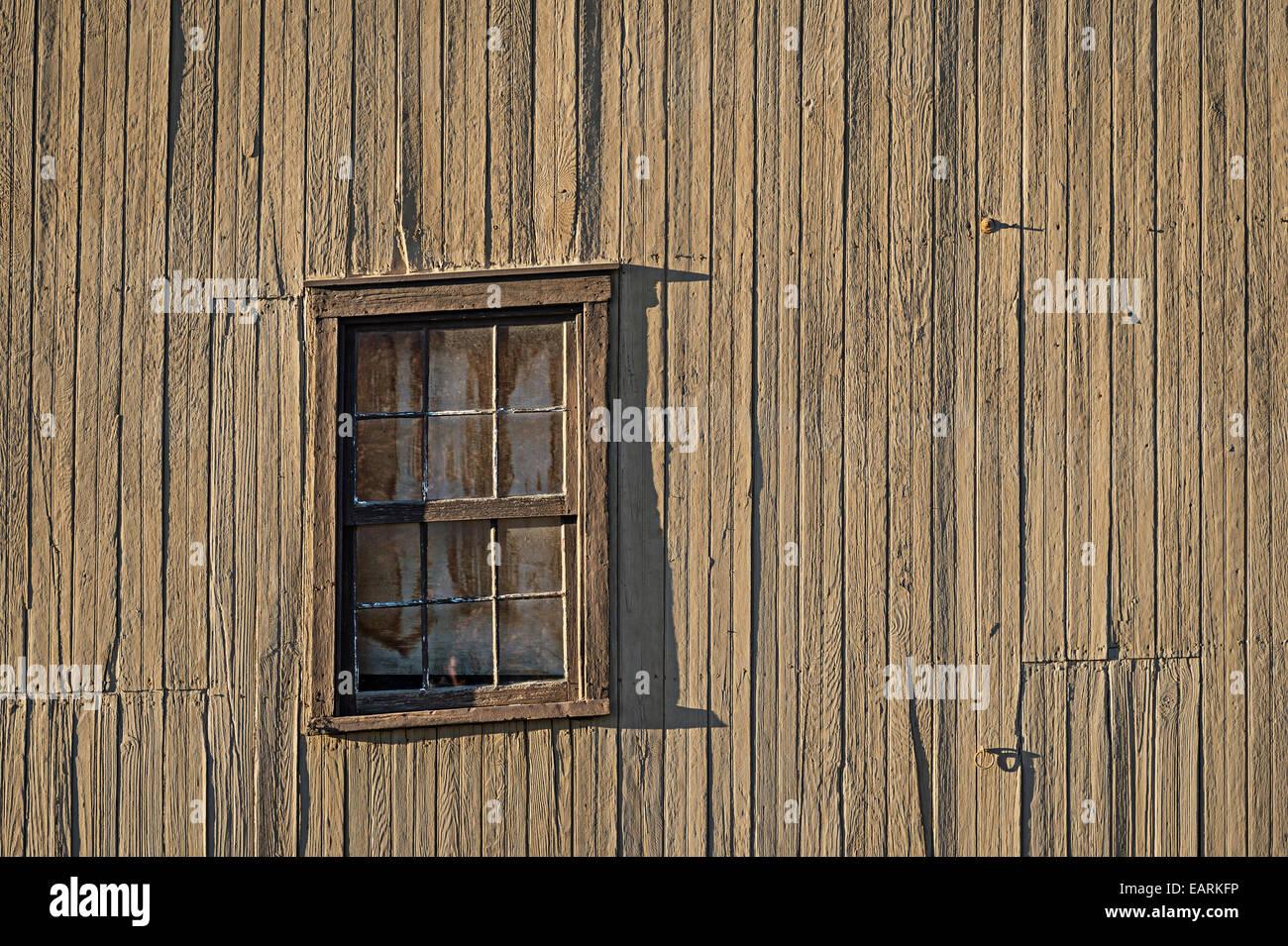 Old Slanted Window On Ramshackle Dilapidated Barn - Stock Image
