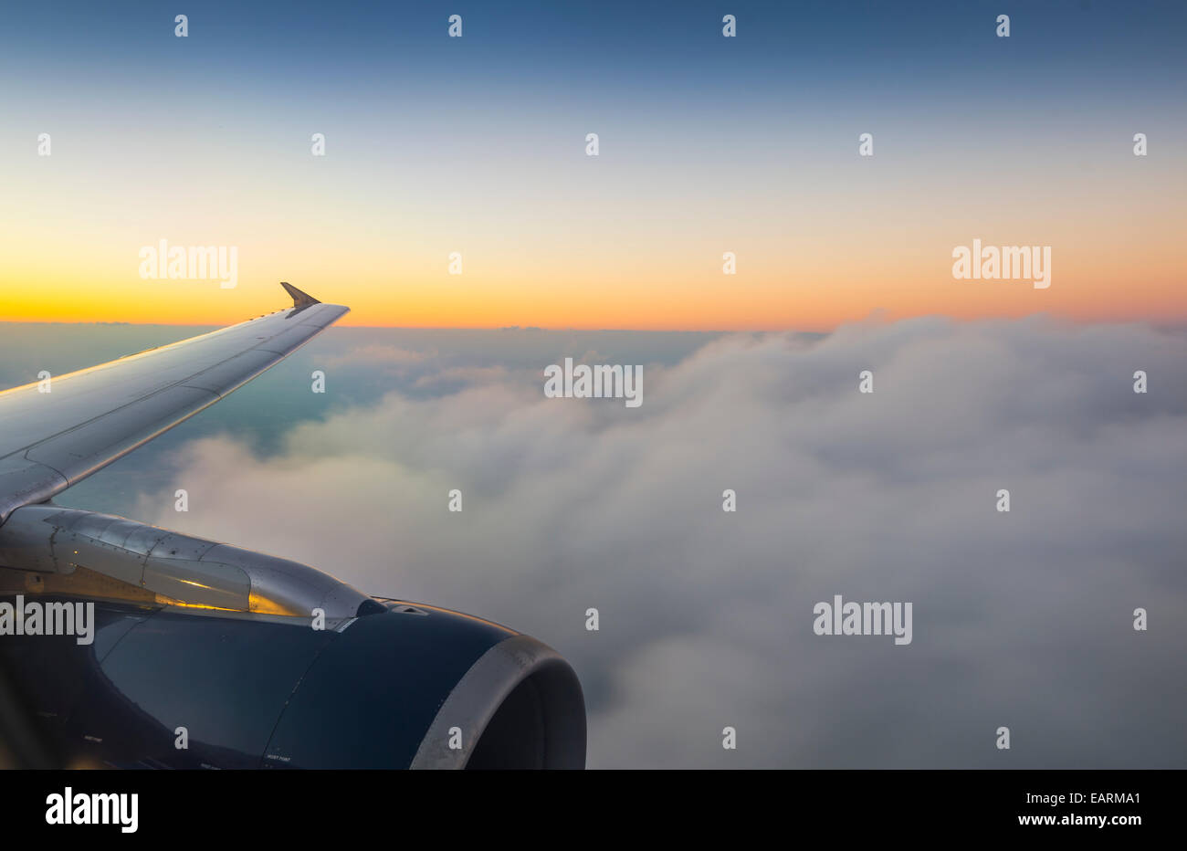 Airplane Wing And Clouds With Sunset - Stock Image