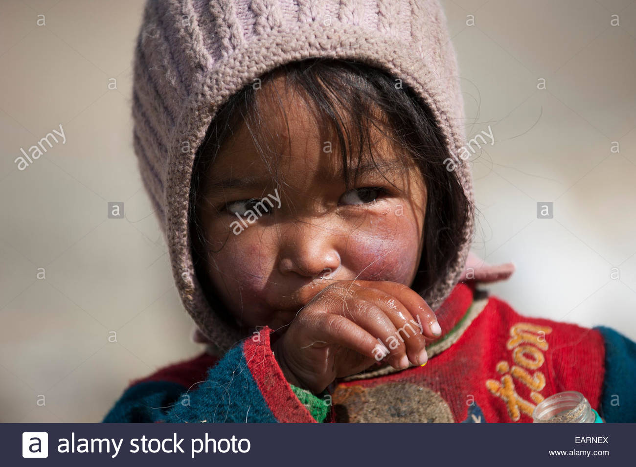 A little nomad shows the effects of exposure in her weathered face. - Stock Image