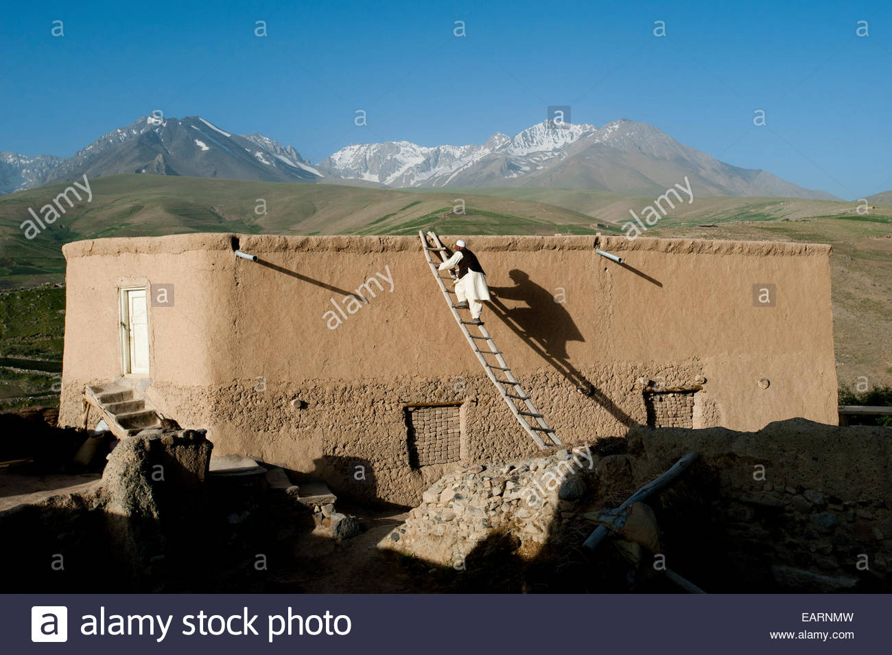 A farmer climbs up onto his roof to get a better view. - Stock Image