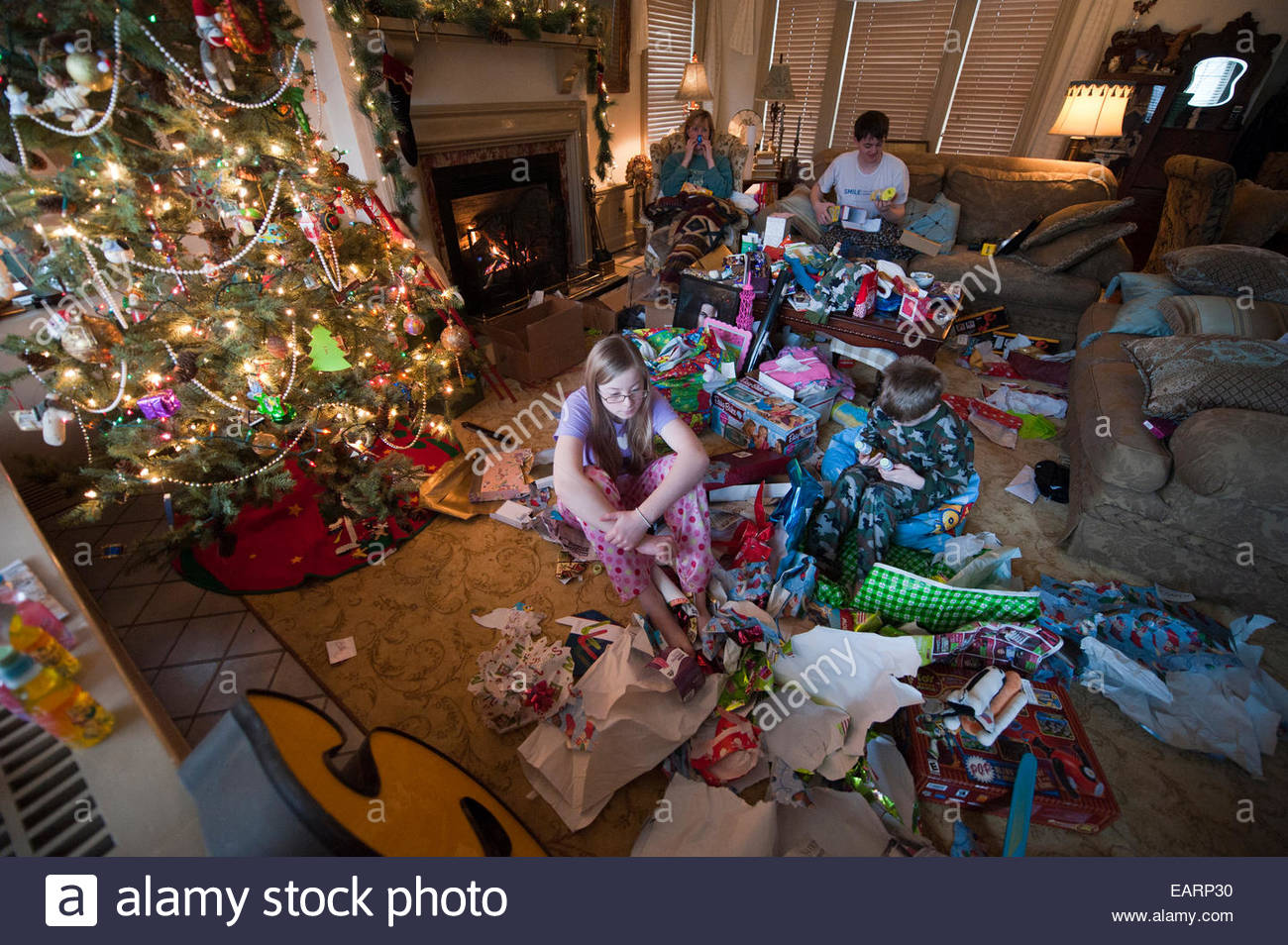 A family opens gifts together on Christmas morning. - Stock Image