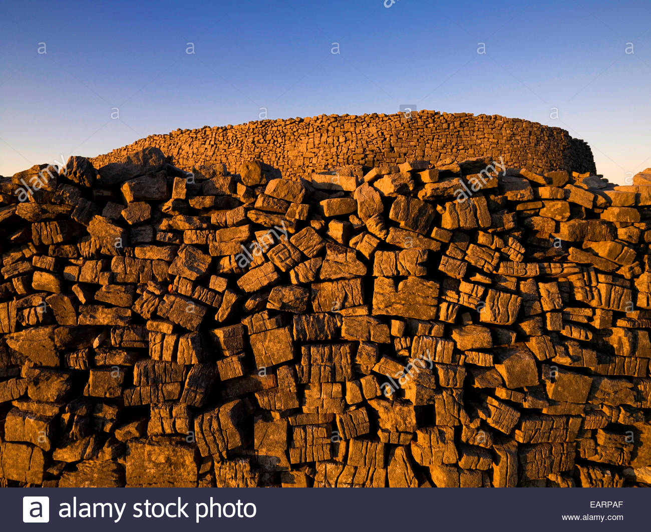 Sun setting on the Stone wall of Dun Aengus on the Aran Islands. - Stock Image