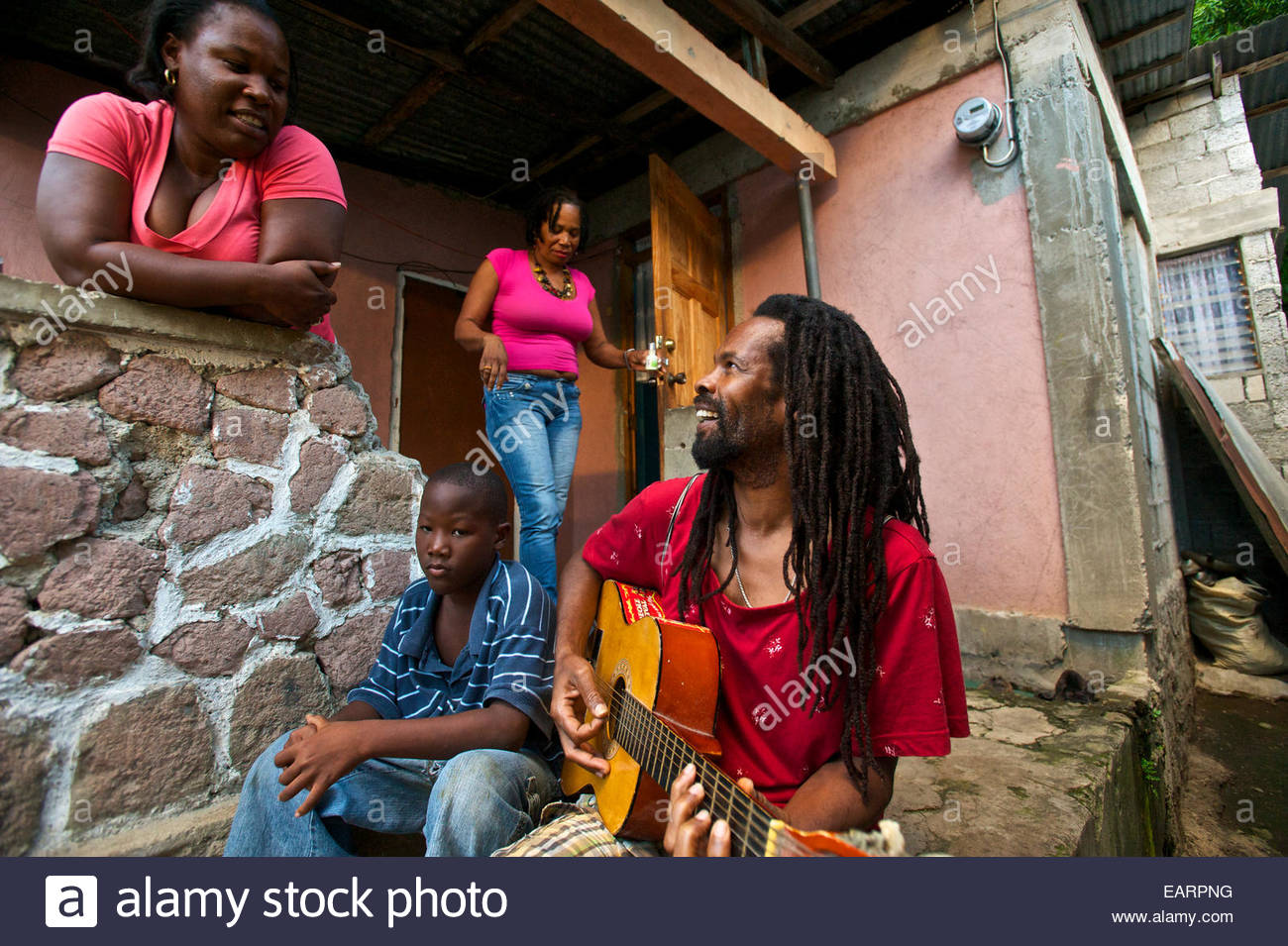 Damian Fontaine, a rastafarian singer, talks with his family at home. - Stock Image