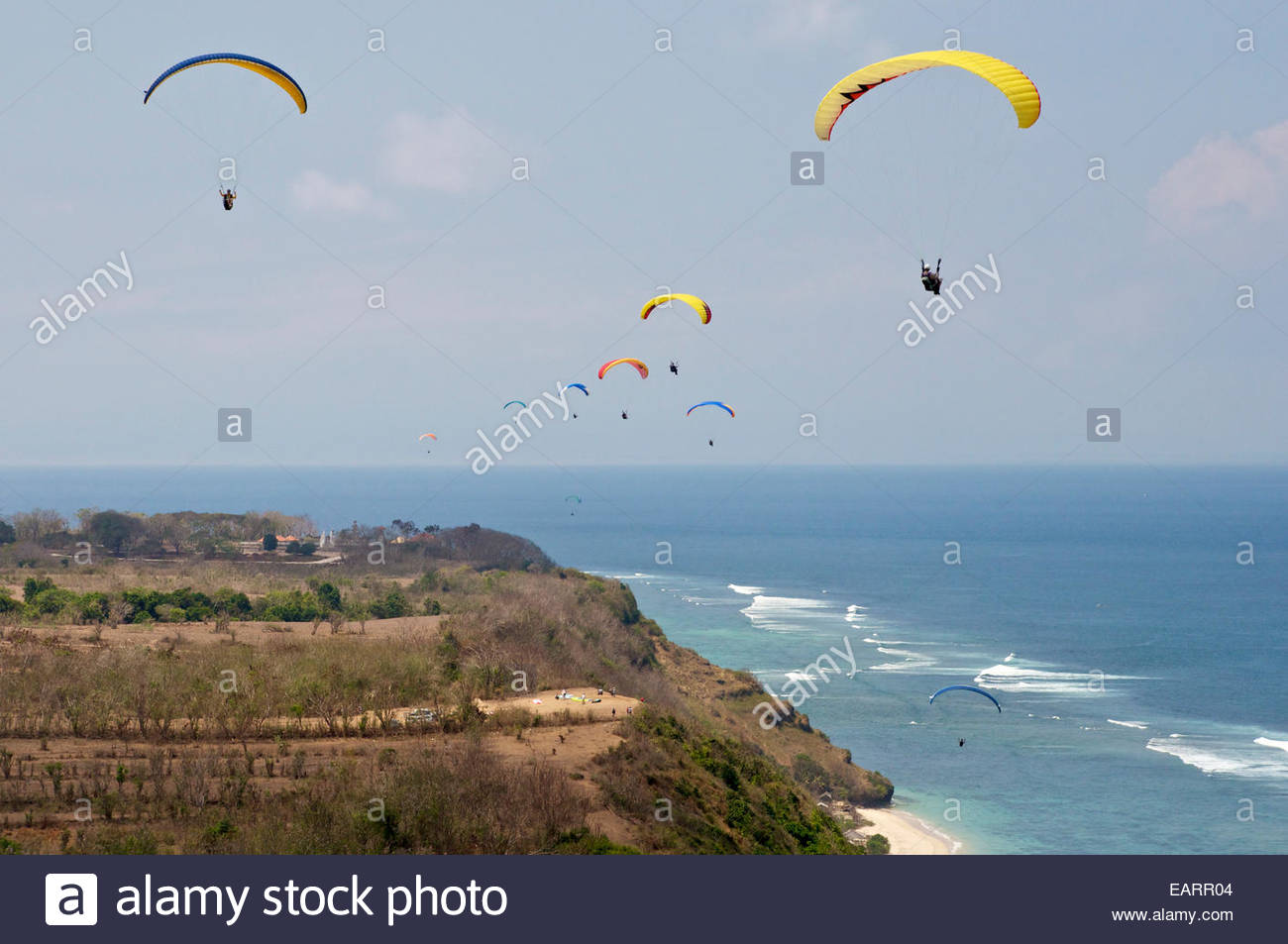 Paragliders soar Bali's coastline in afternoon seabreeze conditions. - Stock Image