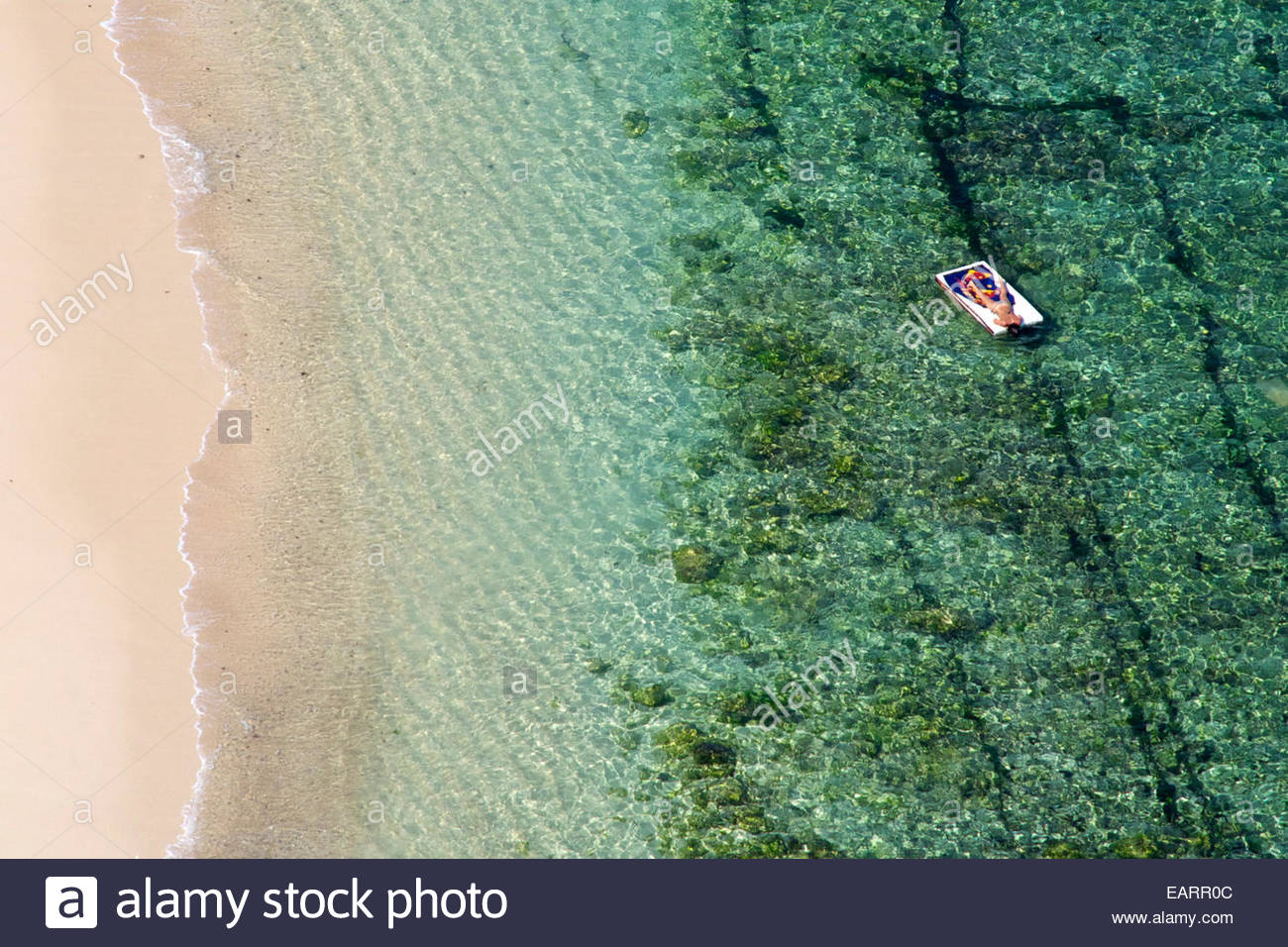 A lone sunbather relaxes on a floating bed, by the beach. Stock Photo