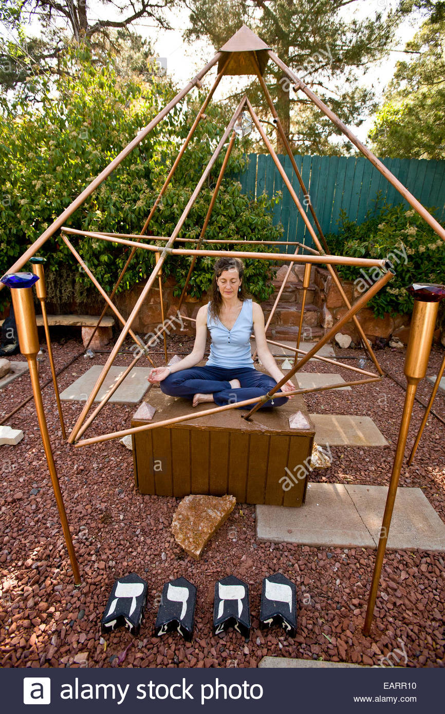 A woman meditates under a copper pyramid to channel energy upward
