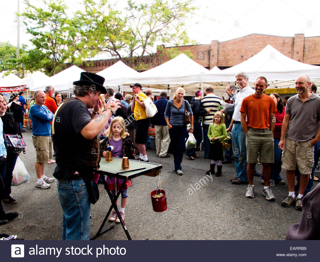 A man performs magic tricks in front of crowd at local farmers market. - Stock Image