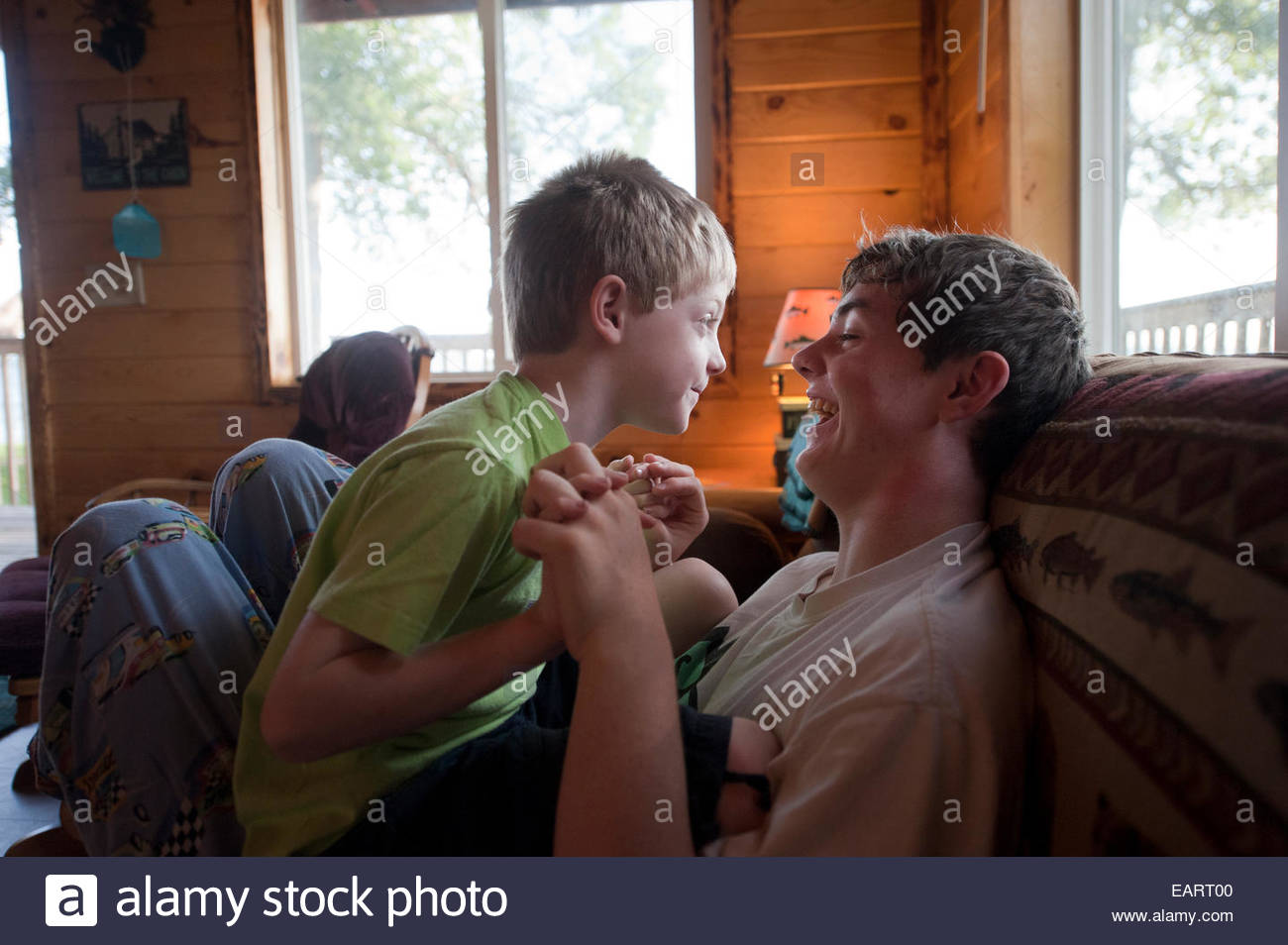 A young boy tries to wrestle with his older brother. - Stock Image