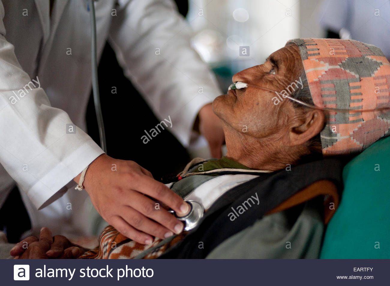 A doctor listens to an old mans hearthbeat with a stethoscope. - Stock Image