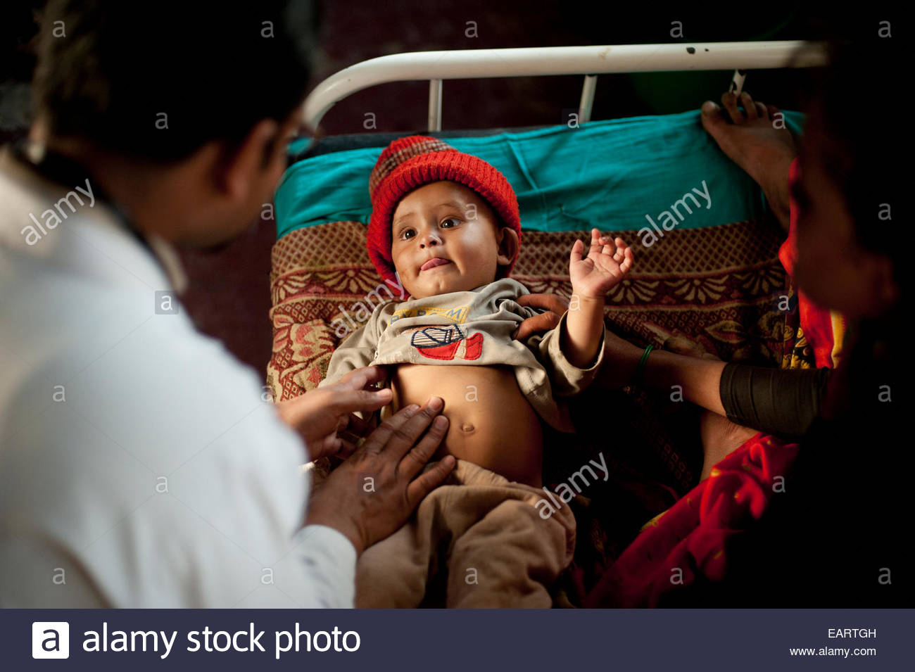 A doctor examines a small baby who is suffering from pneumonia. - Stock Image