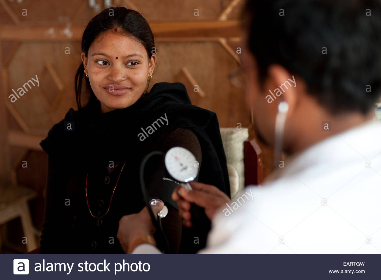 A doctor checks a woman's blood pressure in a hospital in rural Nepal. - Stock Image