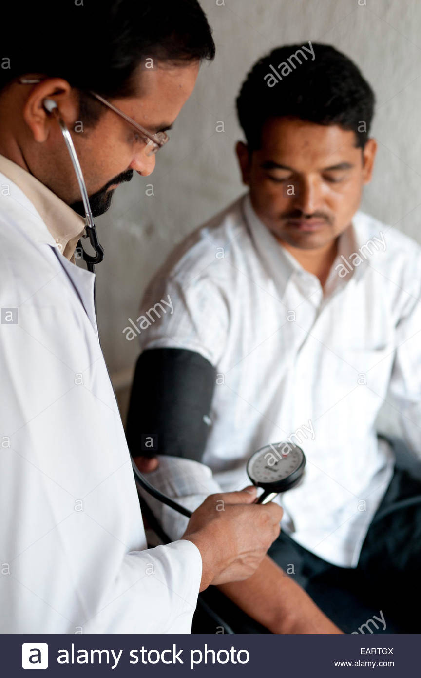 A doctor checks a man's blood pressure in a hospital in rural Nepal. - Stock Image