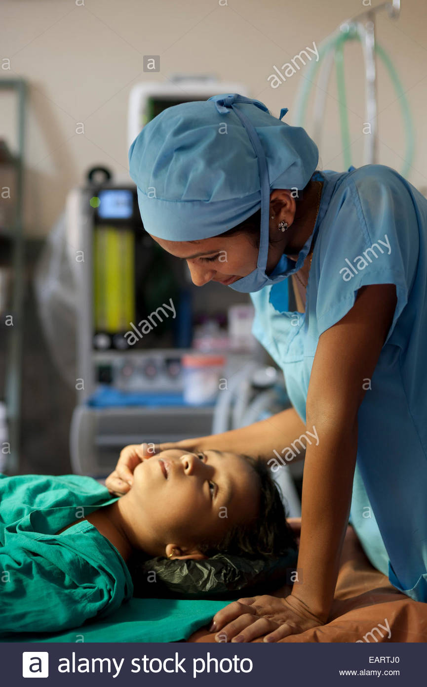 A nurse checks a boy after he has received general anaesthetic. - Stock Image