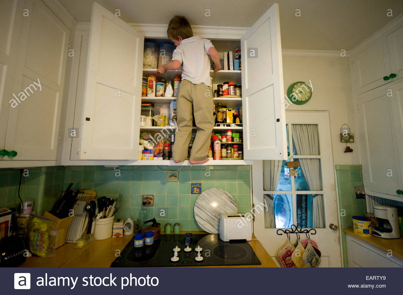 A young boy climbs the cabinets in a kitchen looking for food. Stock Photo