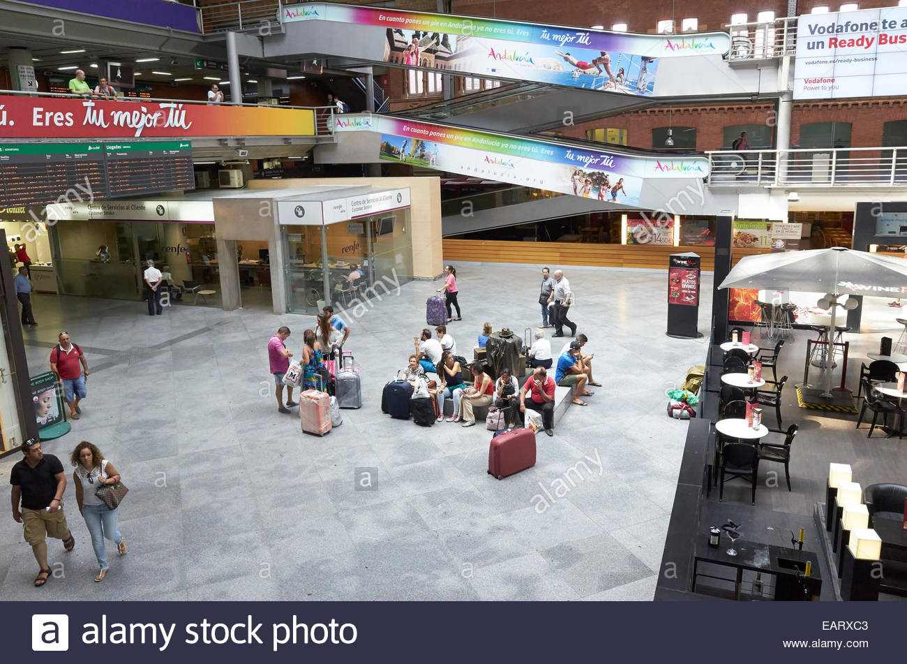 Interior of Atocha Railway Station in Madrid with commuters and restaurant area with diners seen from above - Stock Image