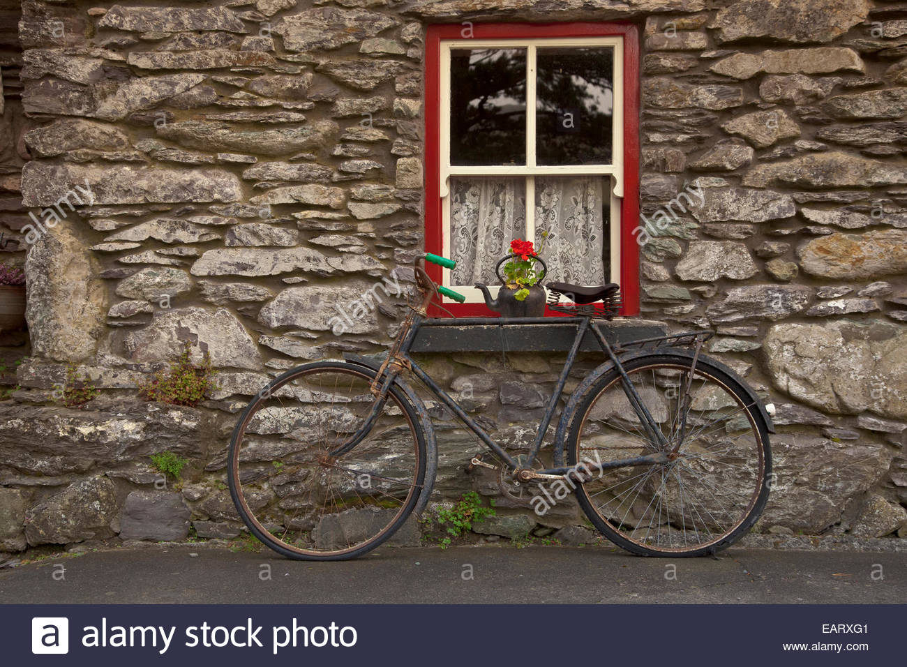 An old bicycle rests against an old stone house. - Stock Image
