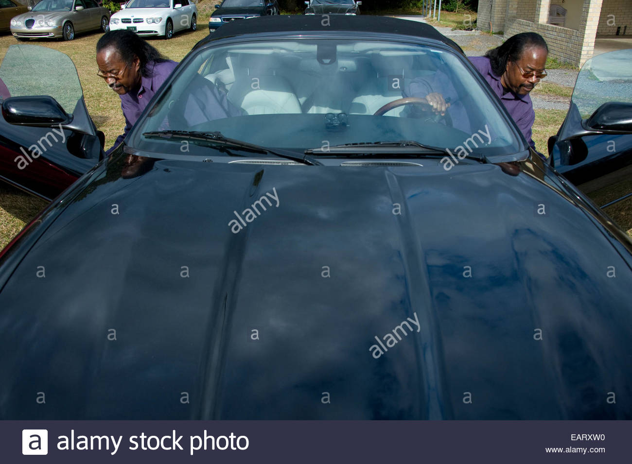 Twin brothers with one of their collectible cars. - Stock Image