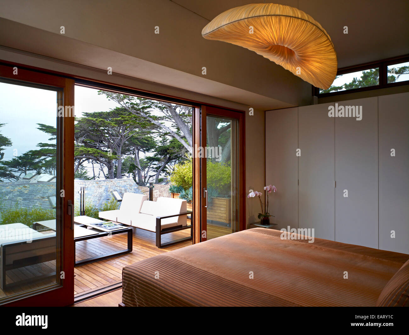 Pendant Light Above Double Bed In Bedroom With View To Balcony Stock