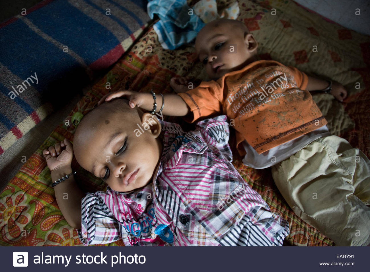 A nine month old twin touches his sleeping brother. - Stock Image