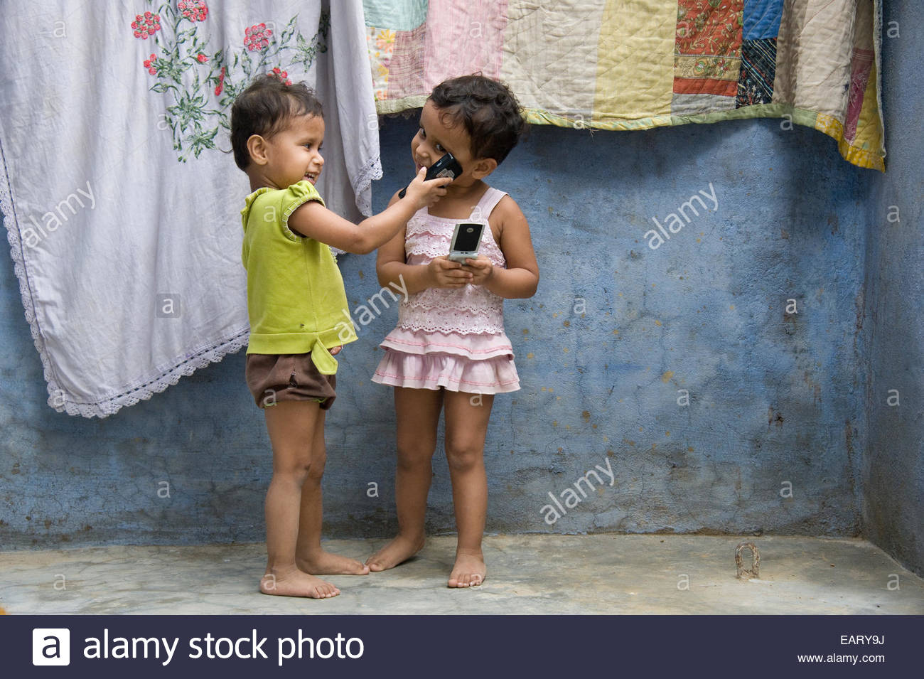 Twin girls play with mobile telephones outside their home. - Stock Image