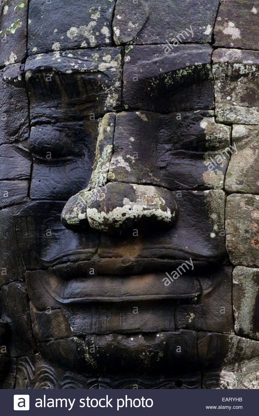 A carved stone face at Bayon Temple. - Stock Image