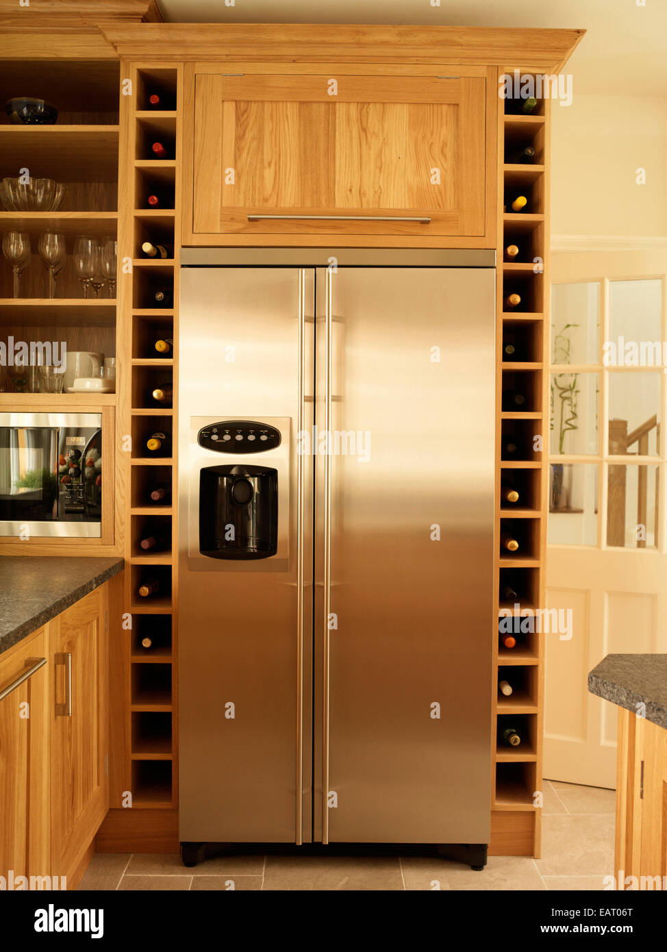 Stainless steel fridge and built in wine rack storage in kitchen ...