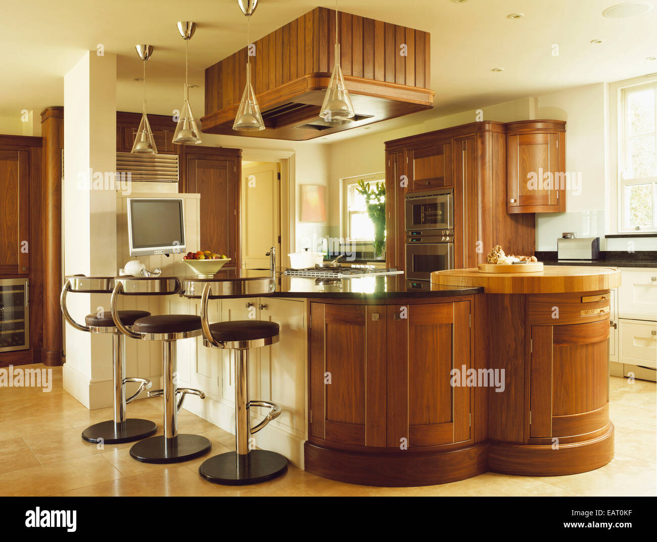 Bar stools at breakfast bar with wooden units in contemporary ...