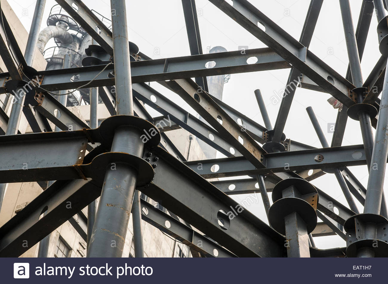 Steel beams overlap each other next to a decommissioned factory. - Stock Image