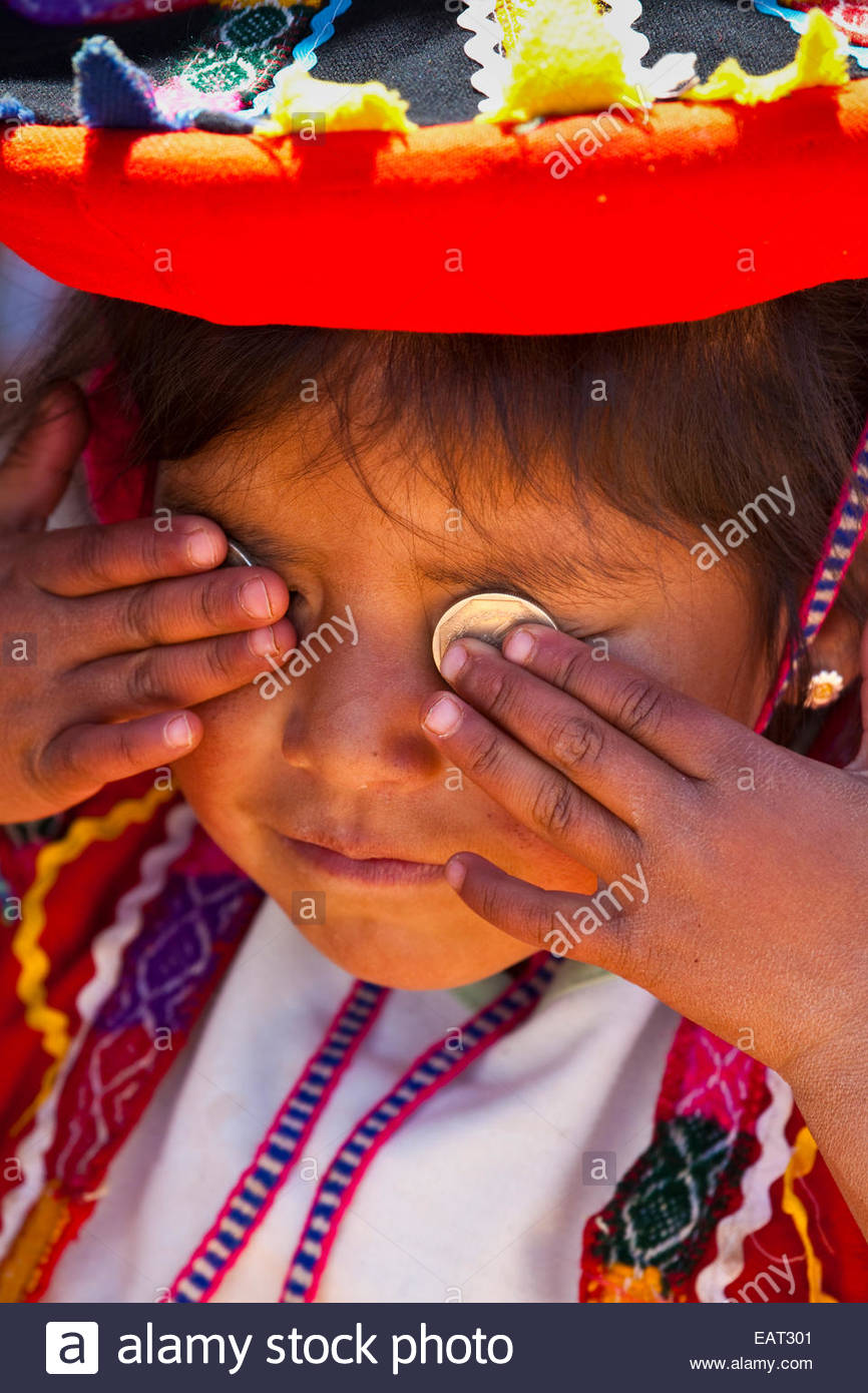 A little girl puts coins worth Dos Soles on her eyes. - Stock Image
