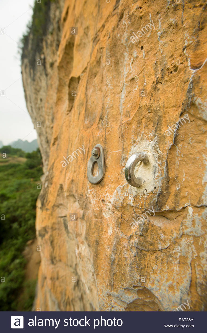 A defaced rock climbing anchor next to a new one. - Stock Image