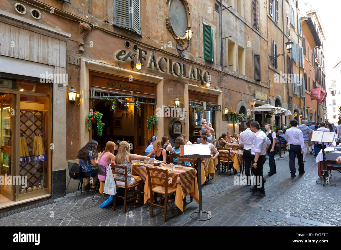 People Dining In Traditional Restaurants In Narrow Street In