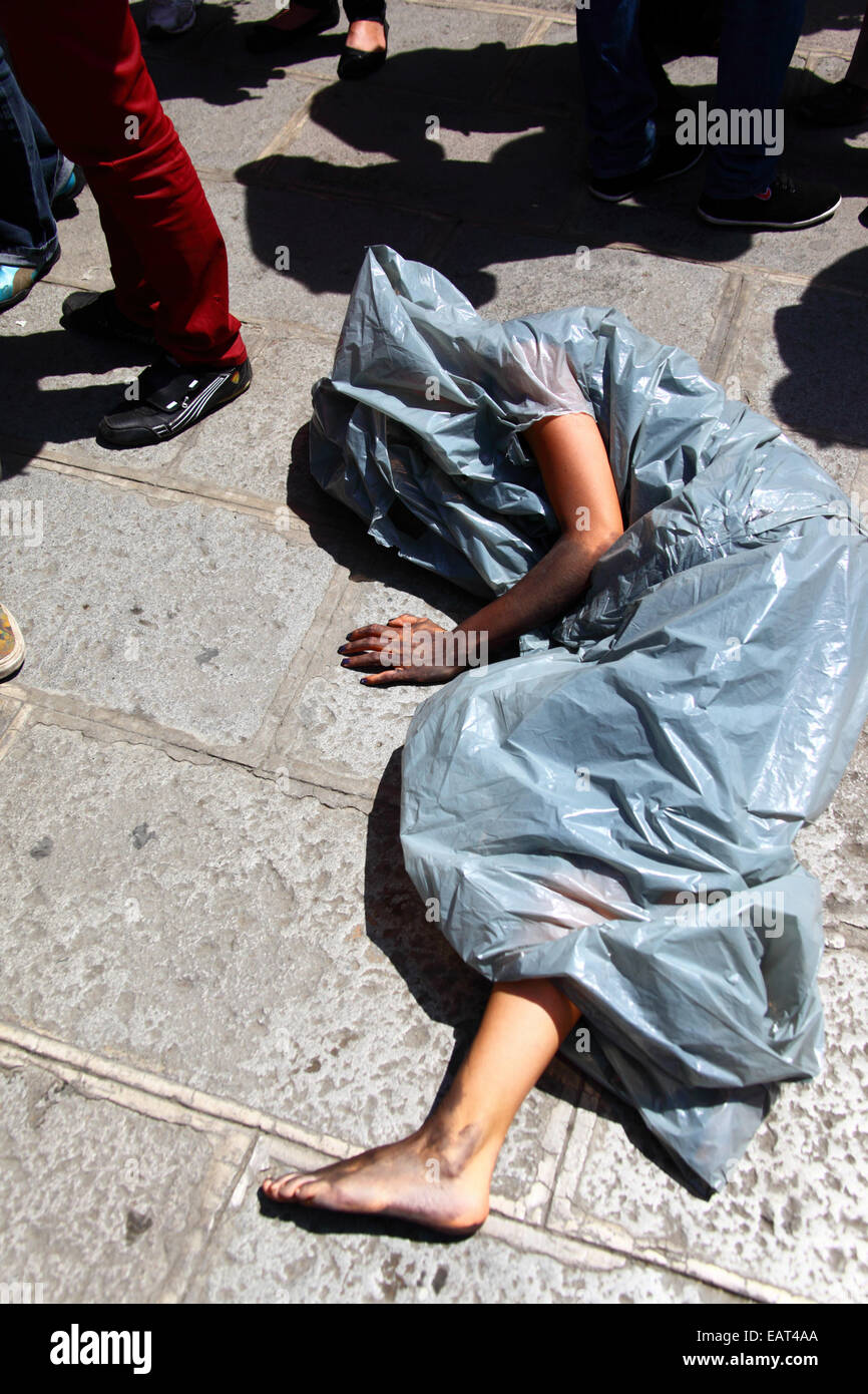 La Paz, Bolivia. 20th November, 2014. A protester lies on the ground in a plastic bag representing a body bag before - Stock Image