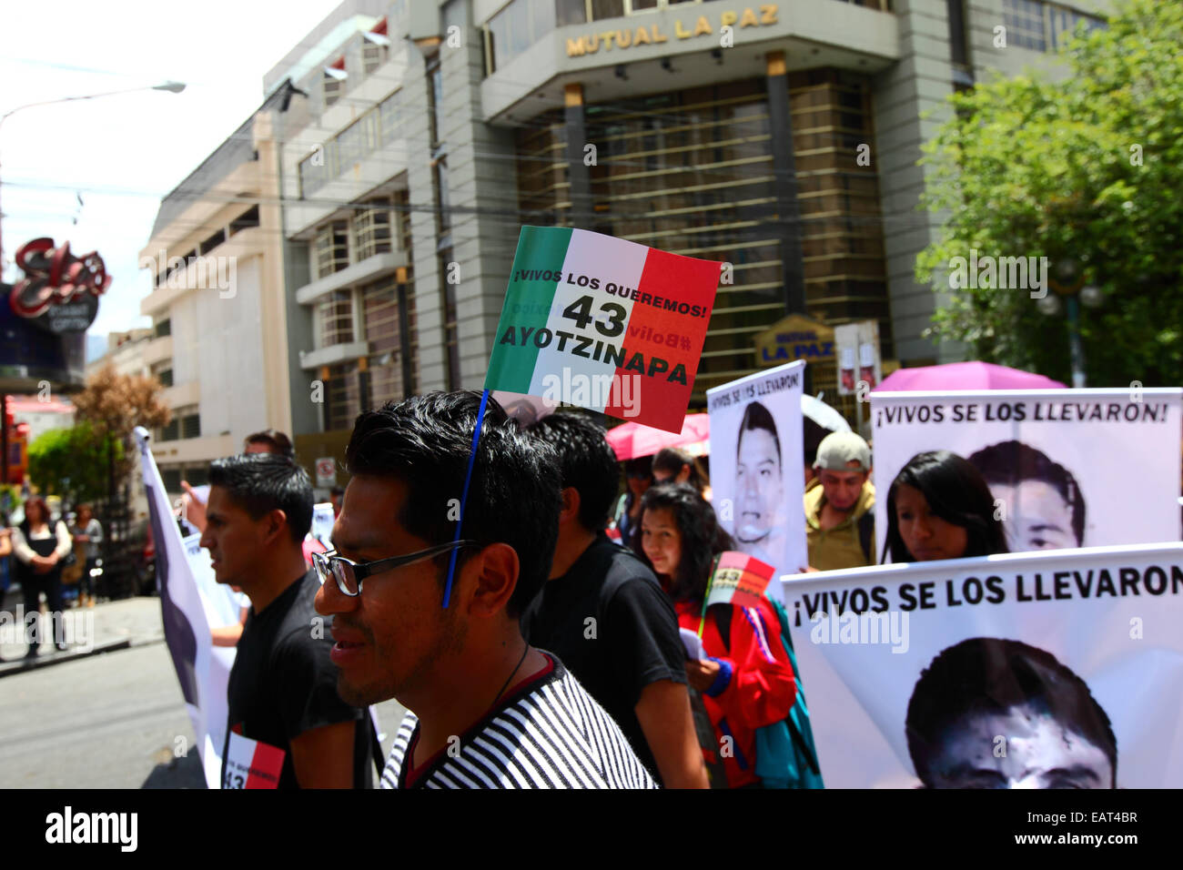 La Paz, Bolivia. 20th November, 2014. A protester wears a Mexican flag with 43 Ayotzinapa on it during a march to Stock Photo