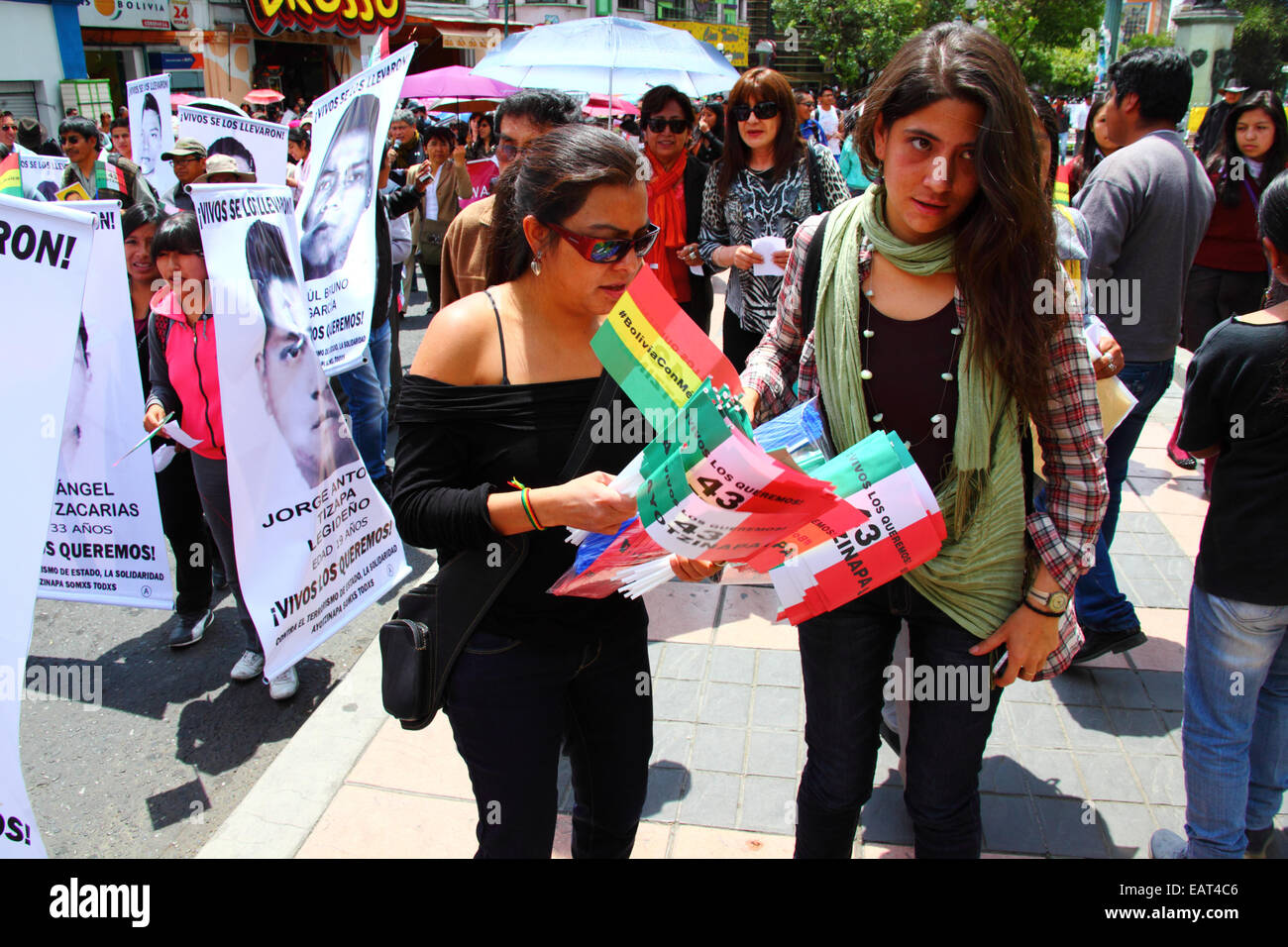La Paz, Bolivia. 20th November, 2014. Protesters hand out flags with 43 Ayotzinapa on them during a march to demand Stock Photo