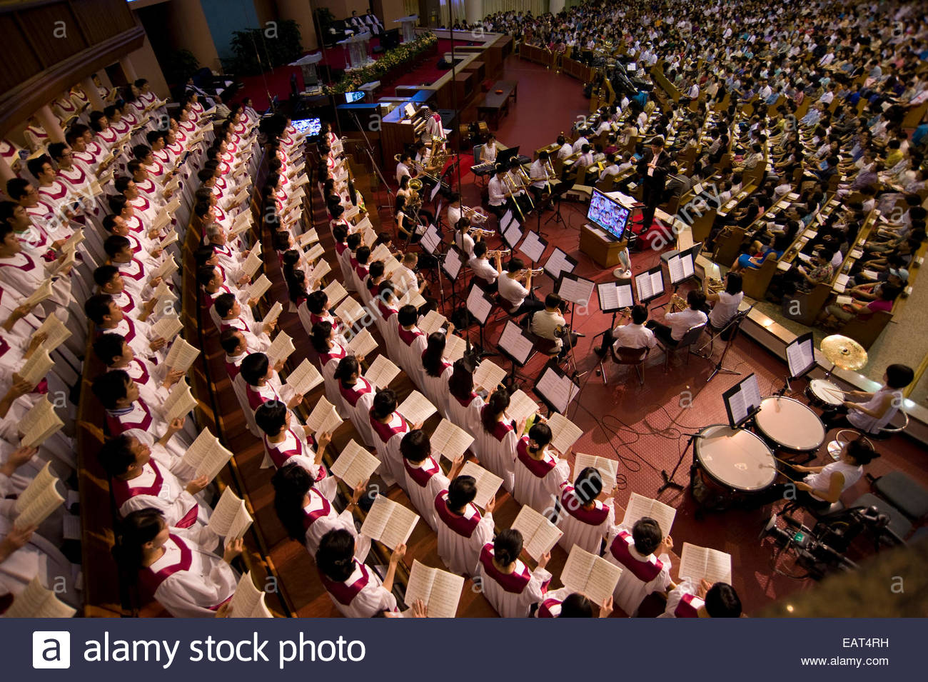 The congregation joins the choir in a hymn during church service. - Stock Image
