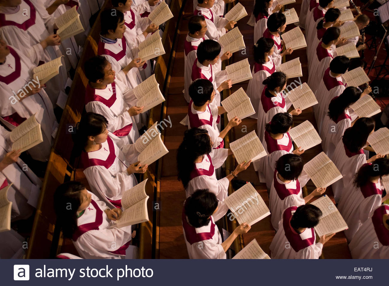 The church's choir sings from their hymnals during church service. - Stock Image