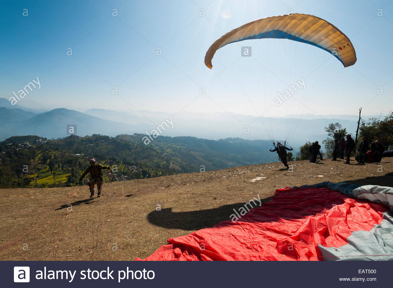 A paraglider launches from the top of Sarankot near Pokhara - Stock Image