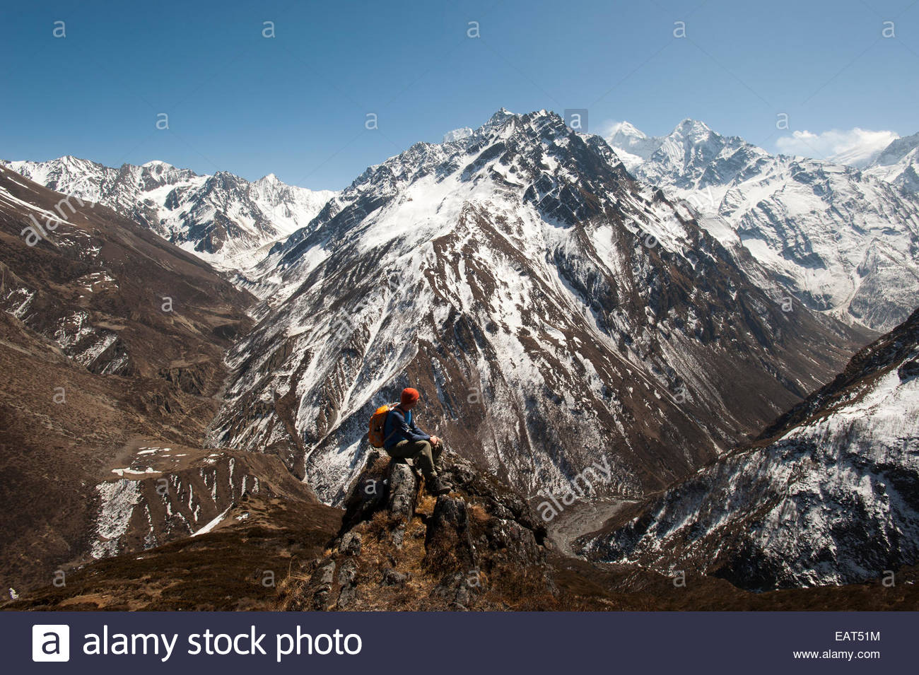 A trekker looks out at the view of Ganesh Himal mountains in Nepal - Stock Image