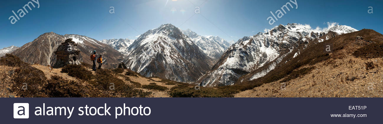 Trekkers look out at the awesome view of Ganesh Himal mountain range - Stock Image