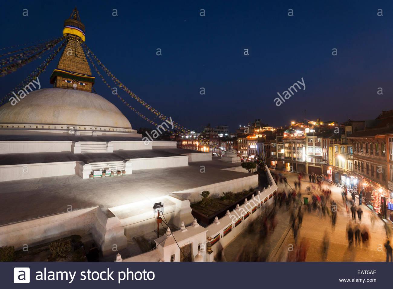 Tourists and pilgrims circle the Buddhist stupa of Baudda in Kathmandu - Stock Image