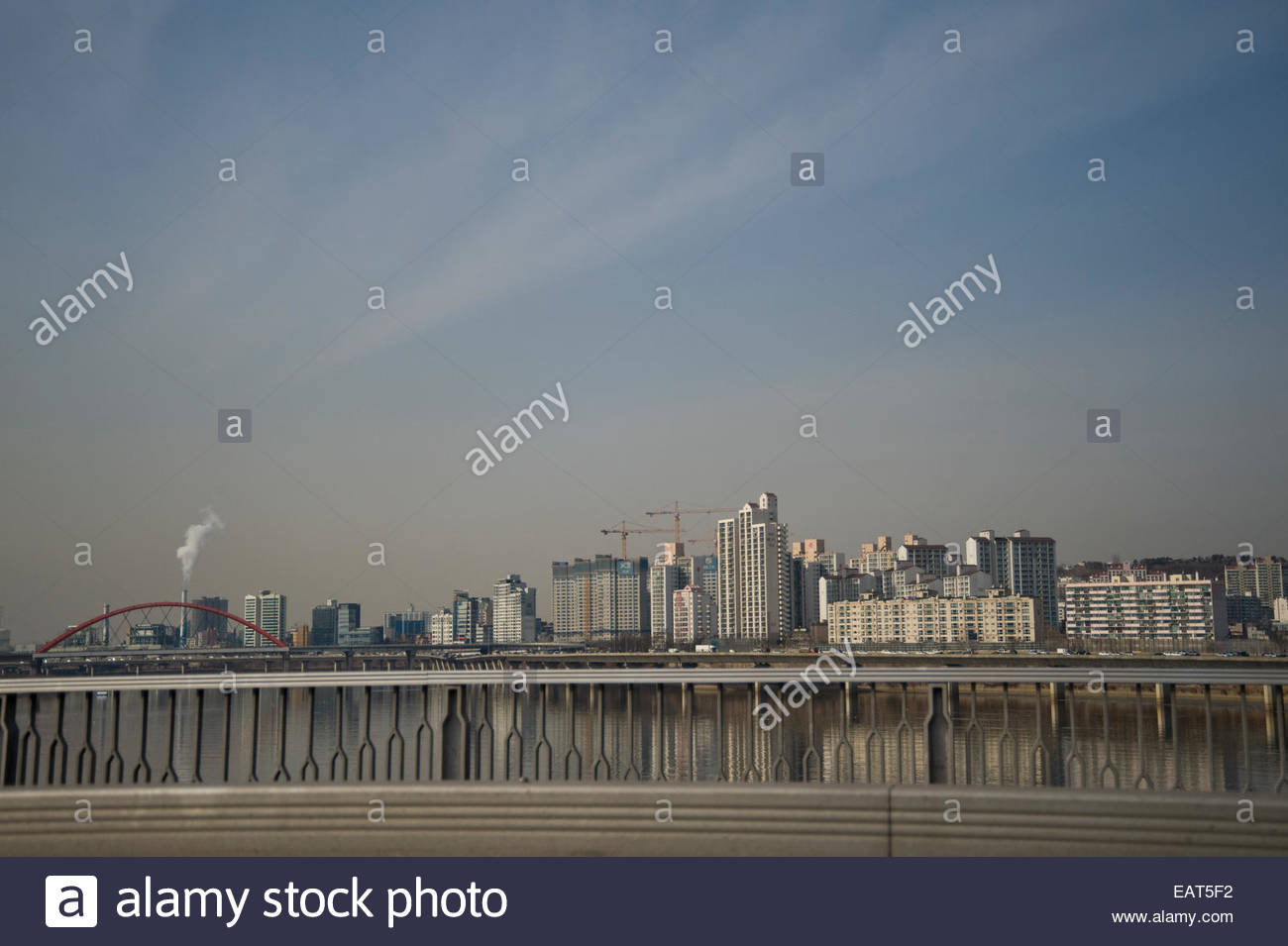 The city's skyline rises above the bridge over Han River. - Stock Image